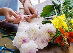 One of our designers carefully arranges a variety of mixed flowers